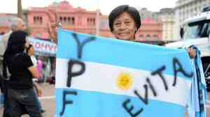 A woman holds an Argentine national flag in front of the presidential pa