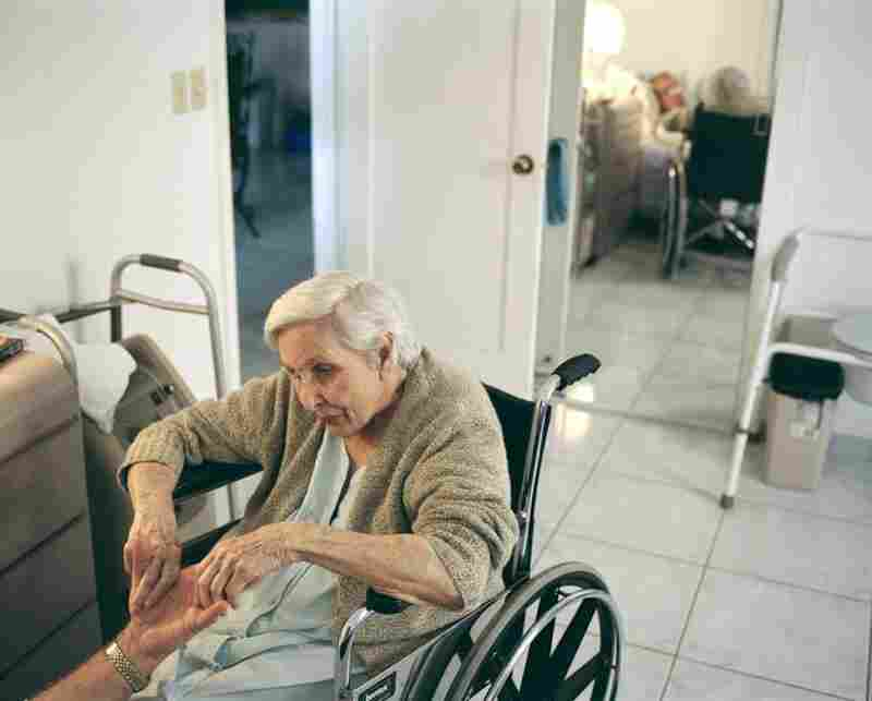 """Estela massaging her son Pedro's hand, Miami, Florida, 2005Pedro visited his mother, Estela, 89, several times a week at an assisted-living facility near his house. While she was unable to speak due to Parkinson's disease, she still responded well to touch. After massaging her hands with lotion, Pedro jumped on her bed and exclaimed """"My turn!"""""""
