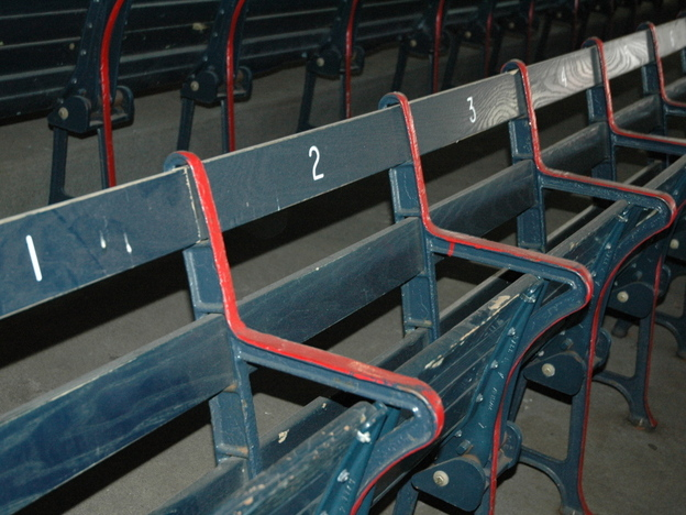 "Fenways boasts ""the oldest seats in baseball."" Owners purposely decided not to sandblast the layers of paint, but rather to let these right field grandstand seats show their history and their age."