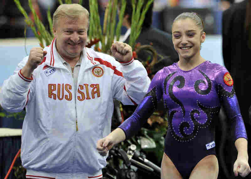 Aliya Mustafina celebrates with her coach, Alexander Alexandrov, after winning the gold medal in the women's individual all-around at the 2010 World Championships in the Netherlands. She suffered injuries that prevented her from competing in 2011.