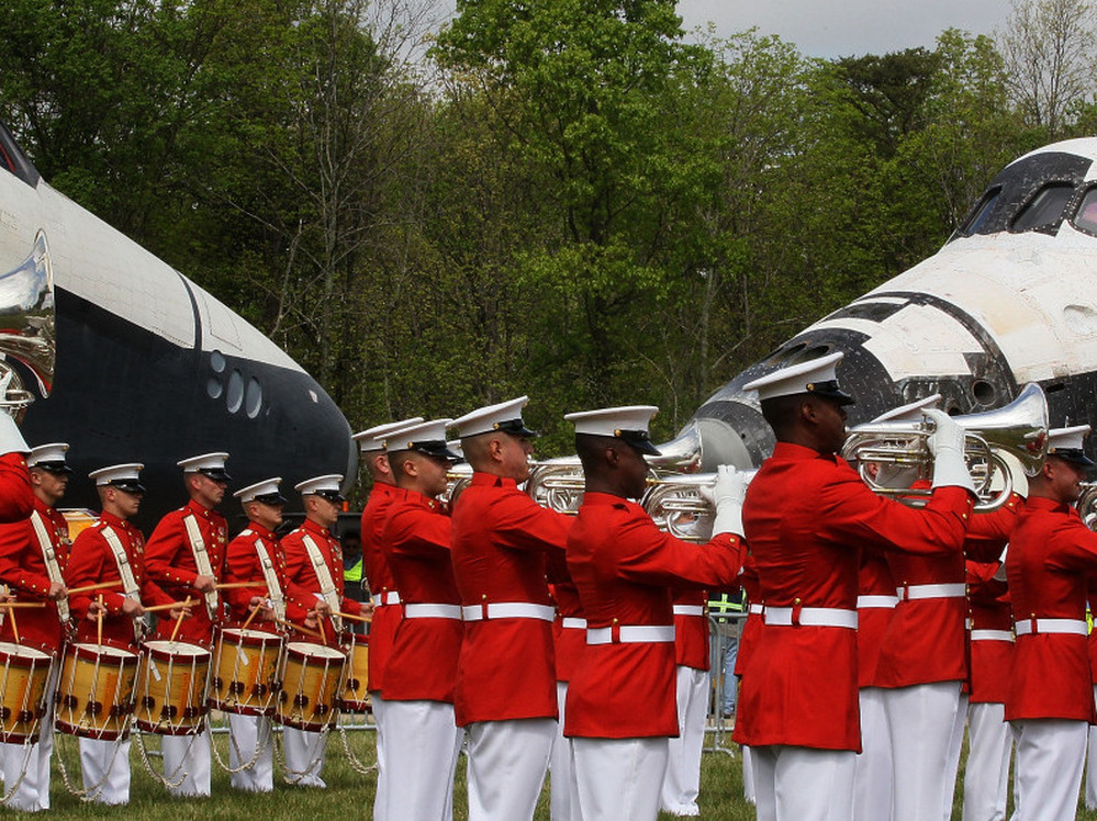 A military band plays as the Space Shuttle Discovery (R), and the Space Shuttle Enterprise (L), sit nose to nose, during an event at the Smithsonian National Air and Space Museum Steven F. Udvar-Hazy Center April 19, 2012 in Chantilly, Virginia.