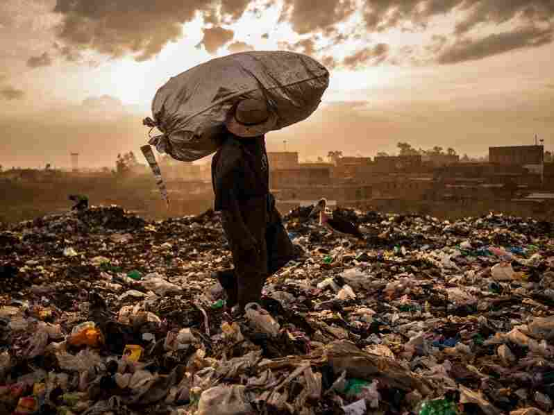 A man from the slum of Korogocho hefts his last bag of trash for the day in hopes of selling the mostly rubber scraps. He'll earn fifty cents for the lot.