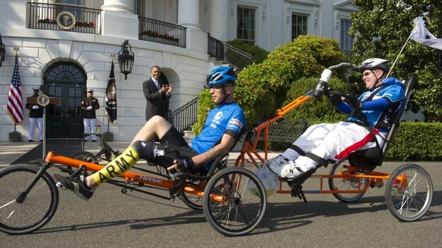 Brothers Deven (left) and Erik Schei ride by President Barack Obama on the South Lawn of the White House as part of the sixth annual Wounded Warrior Project's Soldier Ride on Friday.