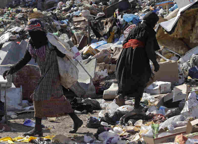 People sift through trash at a garbage dump in Baghdad, Iraq.