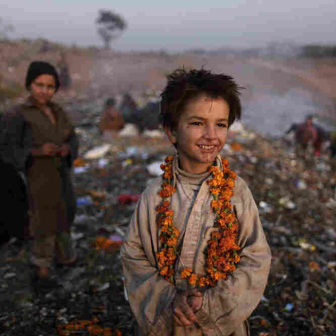 Afghan refugee Shafiq Mohammed, 9, and other children look for items of use on the outskirts of Islamabad, Pakistan, in December.