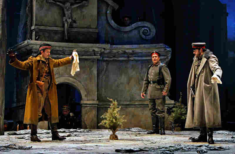It's Christmas Eve on the battlefield. German opera singer Nikolaus Sprink (William Burden, center) wades into no man's land with a small Christmas tree, inspiring a sudden cease-fire. He's accompanied by Scotsman Lieutenant Gordon (Gabriel Preisser, left) and German Lieutenant Horstmayer (Craig Irvin).