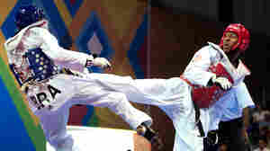 Terrence Jennings (right) lands a kick during a taekwondo match last fall. Jennings, who says his love of the Teenage Mutant Ninja Turtles drew him to the sport, will compete in his first Olympics this summer.
