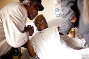 Franklin Brunson (left) and Curtis Gilmore help Natasha's mother, Luella Brunson, sit upright in her hospital bed. Along with caring for her aging father, Natasha keeps a close eye on her 80-year-old mother, who is often hospitalized with complications from chronic obstructive pulmonary disease.