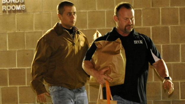 George Zimmerman, left, as he walked out of jail earlier today. The other man was not identified. (AP)