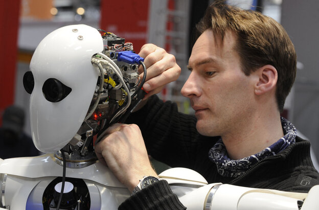 A technician works on the DFKI robot AILA at a German trade fair in 2010.