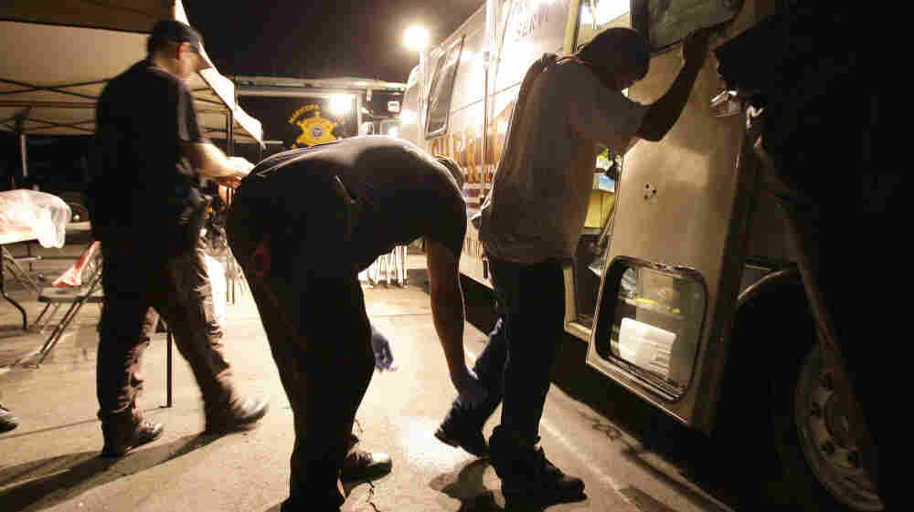 Maricopa County sheriff's deputies check the shoes of a suspect arrested during a crime suppression sweep in Phoenix in 2010. Sheriff Joe Arpaio's immigration and crime sweep came after hundreds of immigrant-rights supporters delayed the effort with a rally at a downtown j