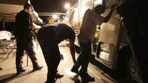 Maricopa County sheriff's deputies check the shoes of a suspect arrested during a crime suppression sweep in Phoenix in 2010. Sheriff Joe Arpaio's immigration and crime sweep came after hundreds of immigrant-rights supporters delayed the effort with a rally at a downtown jail, in opposition to Arizona's immigration law SB 1070.