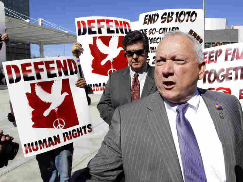 Protesters gather around then-state Sen. Russell Pearce, who sponsored Arizona's immigration law, outside the Sandra Day O'Connor federal courthouse in Phoenix in 2011.