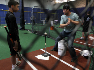 "Reid Gorecki coaches a young player in a batting cage. Remembering the first hit he got in the majors, Gorecki calls it ""a dream come true."""