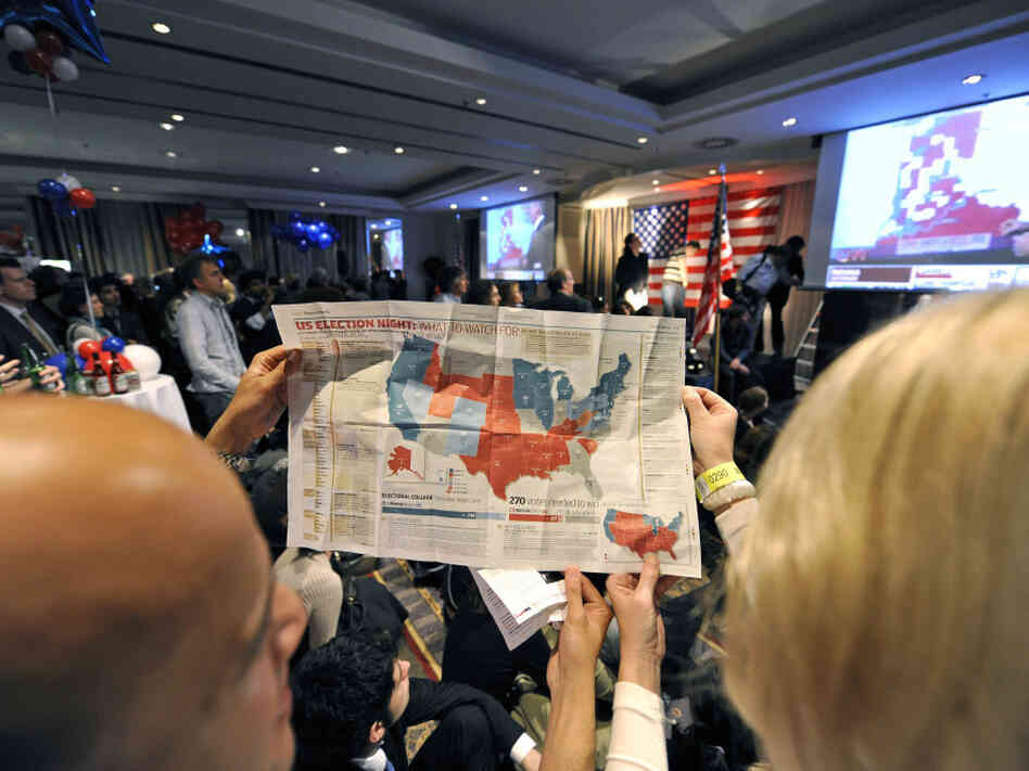 Onlookers study a map of the electoral college system during a Nov. 5, 2008, U.S. presidential election party in Brussels. This year, the electoral vote landscape could be more challenging for Mitt Romney than national popular vote polls might suggest.