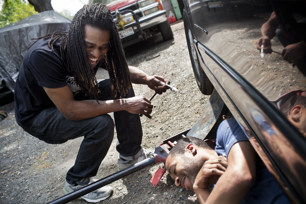 Nicholas (left) laughs with Corey Buford while they work on Nicholas' car. Nicholas has briefly abandoned his music career and is close to getting a job with Comcast.