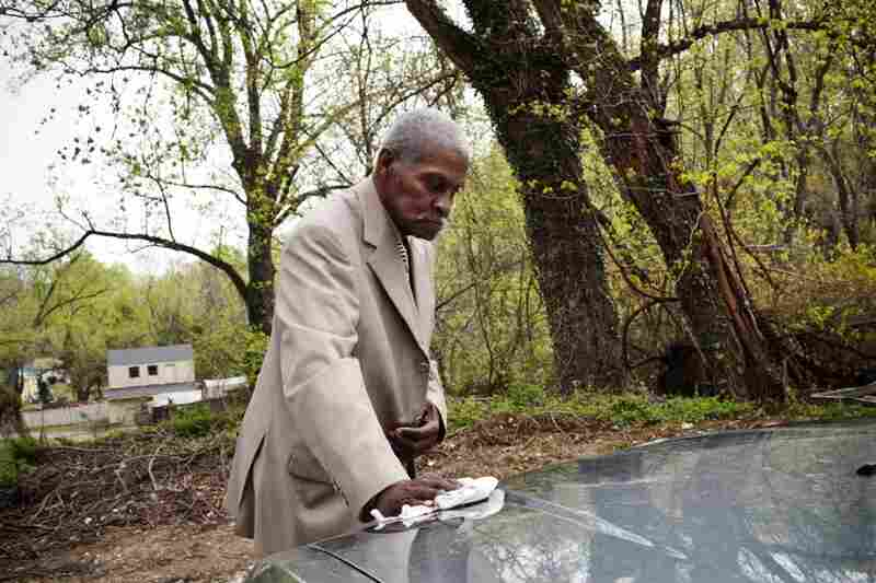Franklin wipes pollen from the family car in their driveway before heading to church on a Sunday morning. He talks often about missing his independence, especially his ability to drive.