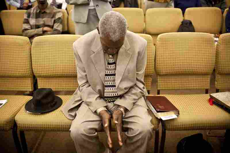 "Franklin prays during Sunday worship. ""I got aches and pains but I can still walk around,"" he says."