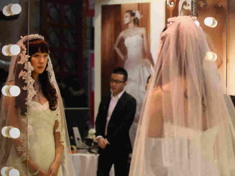 A Chinese woman tries on a wedding dress