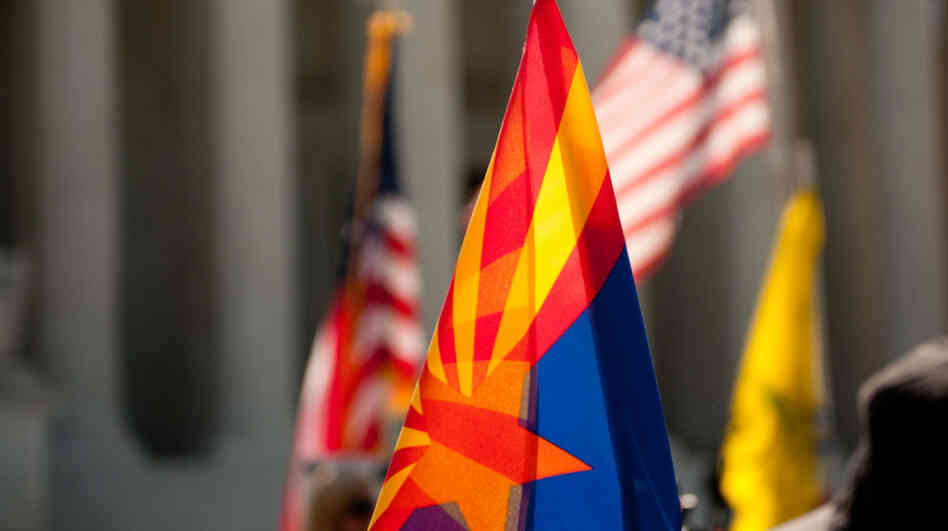 Supporters of Arizona's immigration law fly the flags of the state (center), the United States and the Tea Party on the steps of the Supreme Court during oral arguments about the law on Wednesday.