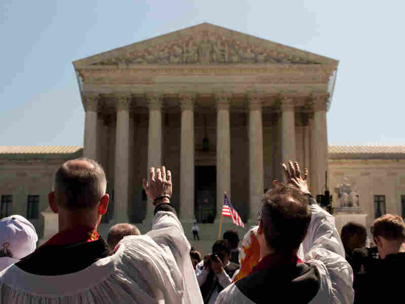 """A group dressed in robes parades in silence around the Supreme Court building in a Bible-inspired """"Jericho Walk."""""""