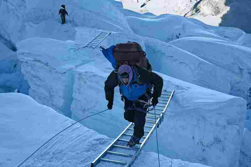 At dawn, a Sherpa runs uphill across a ladder spanning a crevasse at the top of the Khumbu Icefall, April 21.