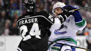 Keith Ballard, right, of the Vancouver Canucks is tripped by Colin Fraser of the Los Angeles Kings for a penalty during game in Los Angeles on April 18. Researchers studying hockey penalties found that teams wearing black jerseys were far more likely to draw penalties than teams wearing other colored or white jerseys.