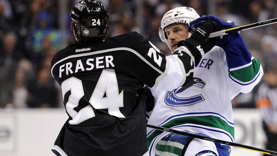 Keith Ballard, right, of the Vancouver Canucks is tripped by Colin Fraser of the Los Angeles Kings for a penalty during game in Los Angeles on April 18. Researchers studying hockey penalties found that teams wearing black jerseys were far more likely to draw penalties than teams wearing other colored or white jerseys. (Getty Images)