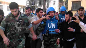 Members of the Syrian opposition walk with a U.N. observer during a visit by monitors to the restive city of Homs, Syria, on April 21. Opposition activists say observers appear to help bring calm if they stay in an area. Two monitors have been deployed in Homs for the past several days.