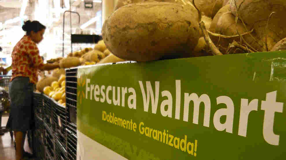 A shopper examines produce at a Wal-Mart store in Mexico City.