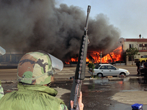 National Guardsmen watch a business go up in flames in South Los Angeles on April 30, 1992. The riots erupted after a mostly white jury acquitted police officers accused in the beating of black motorist Rodney King.