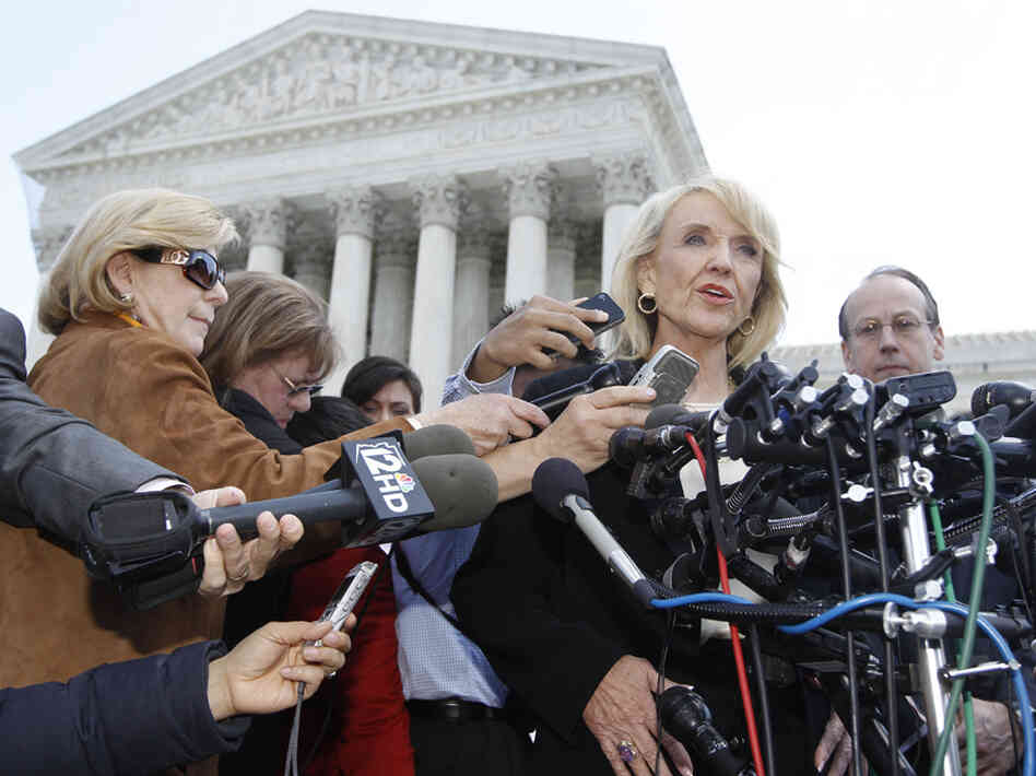 Arizona Gov. Jan Brewer speaks to reporters outside the Supreme Court on Wednesday, after oral arguments on Arizona's immigration law. At left, in brown and wearing sunglasses, is NPR's Nina Totenberg.