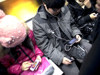 Commuters immersed in their smartphones ride the subway in Beijing.