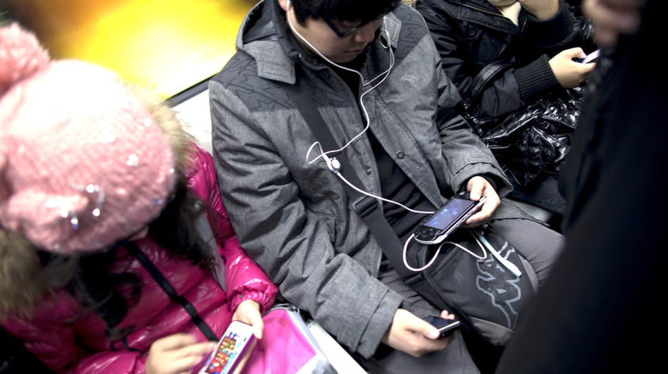 Commuters immersed in their smartphones ride the subway in Beijing. (Bloomberg via Getty Images)