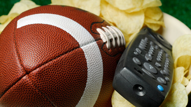 A football and a television remote sit expectantly in a bowl of chips, waiting for an NFL Draft fan to claim them.