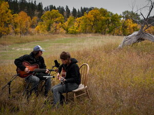 Martha Scanlan performs with Jon Neufeld in a meadow at the ranch where she works.