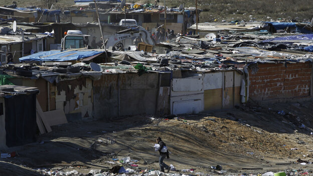 A digger demolishes a shack as a boy walks nearby in one section of the sprawling Cañada Rea