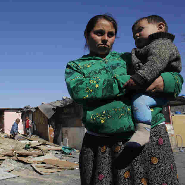 Residents of Cañada Real stand near recently demolished shacks on March 5. The settlement is separated into different sections and tends to be segregated by ethnic groups: Roma in one section, Arabs in another, for example.