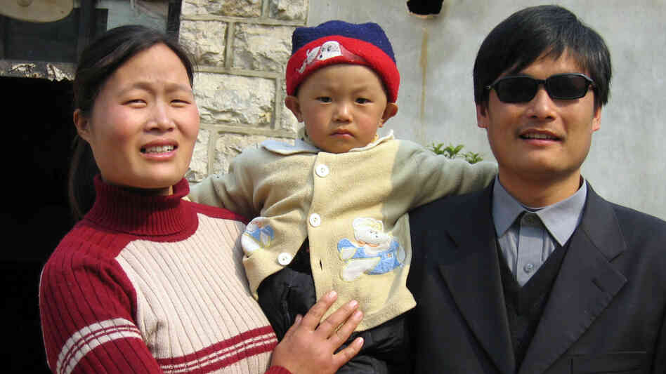 Blind activist Chen Guangcheng with his wife and son outside their home in northeast China's Shandong province in 2005.