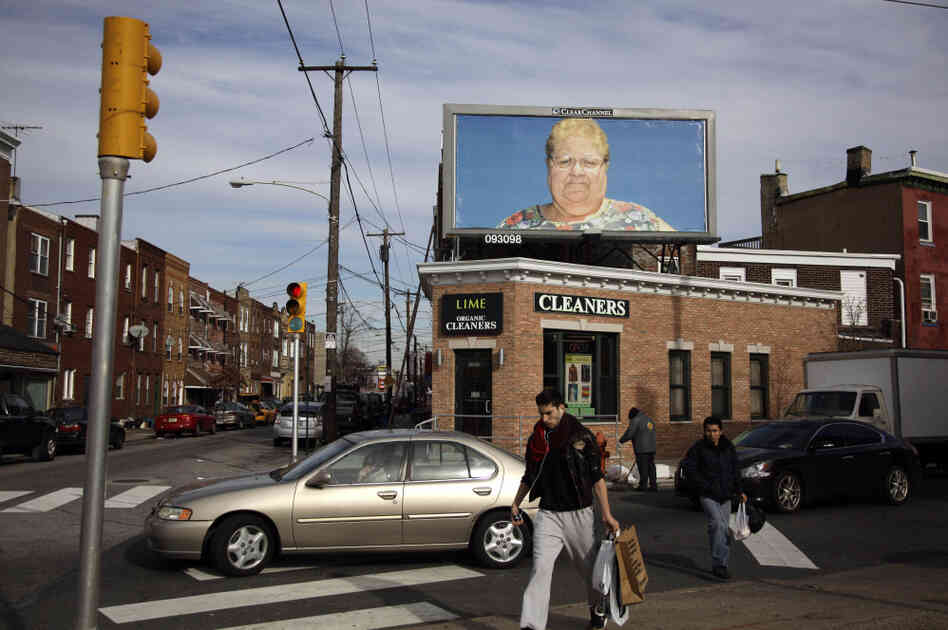 Pedestrians in Philadelphia cross a street in view of a billboard with a photo by Zoe Strauss. Only a dozen years after first picking up a camera to chronicle her beloved hometown's overlooked people and places, Strauss was honored with a solo show at the Philadelphia Museum of Art.