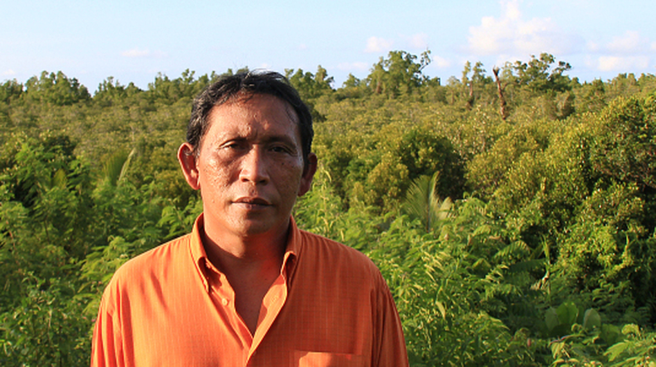 Rignolda Jamaluddin, a local marine scientist, stands in front of the mangrove forests of North Sulawesi that he has worked to rebuild over the past two decades. Part of his strategy included educating villagers on ways they would benefit from not cutting down the trees, such as making alcohol, sugar and furniture from the trees. (Yosef Riadi for NPR)