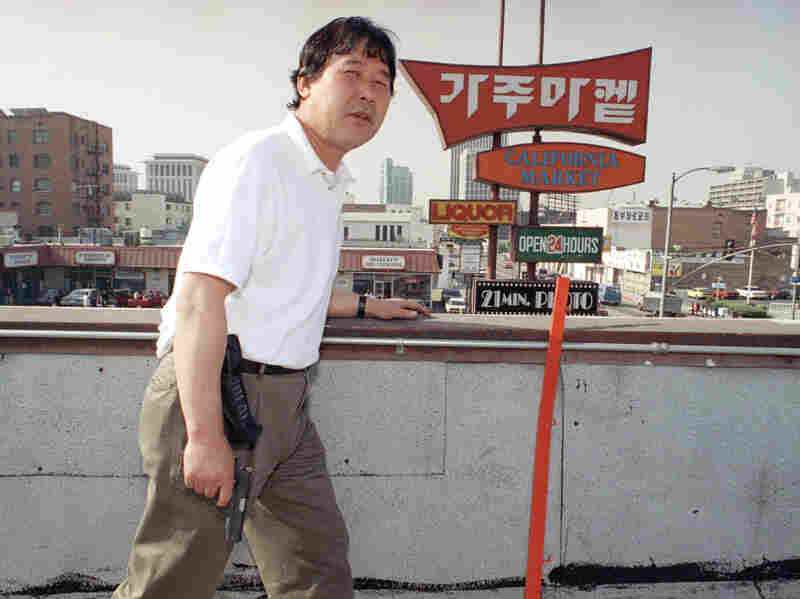 Richard Rhee stands vigil, armed with a handgun and a cellphone, on the roof of his grocery store in the Koreatown area of Los Angeles on May 2, 1992. A disproportionate number of Korean businesses were looted and gutted by fires in the L.A. riots.
