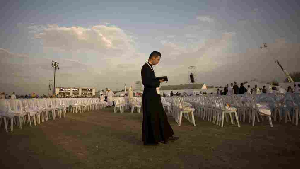 A priest prays before a Mass celebrated by Pope Benedict XVI at the Cuatro Vientos air base outside Madrid during World Youth Day festivities in August 2011. The Catholic Church is hoping to provide an attractive option for young job seekers in Spain, which is suffering from unprecedented unemployment.
