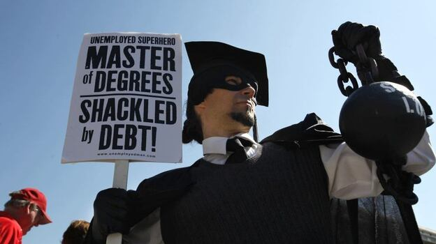 """Gan Golan of Los Angeles, dressed as the """"Master of Degrees,"""" holds a ball and chain representing his college loan debt during Occupy D.C. activities in Washington. Average in-state tuition and fees at four-year public colleges rose an additional $631 this fall, or 8.3 percent, compared with a year ago. (AP)"""