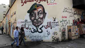 "A mural in Cairo depicts the split faces of Egyptian military ruler Field Marshal Hussein Tantawi, left, and ousted president Hosni Mubarak accompanied by Arabic that reads, ""who assigned you did not die, No for gas export to Israel, the revolution continues."""