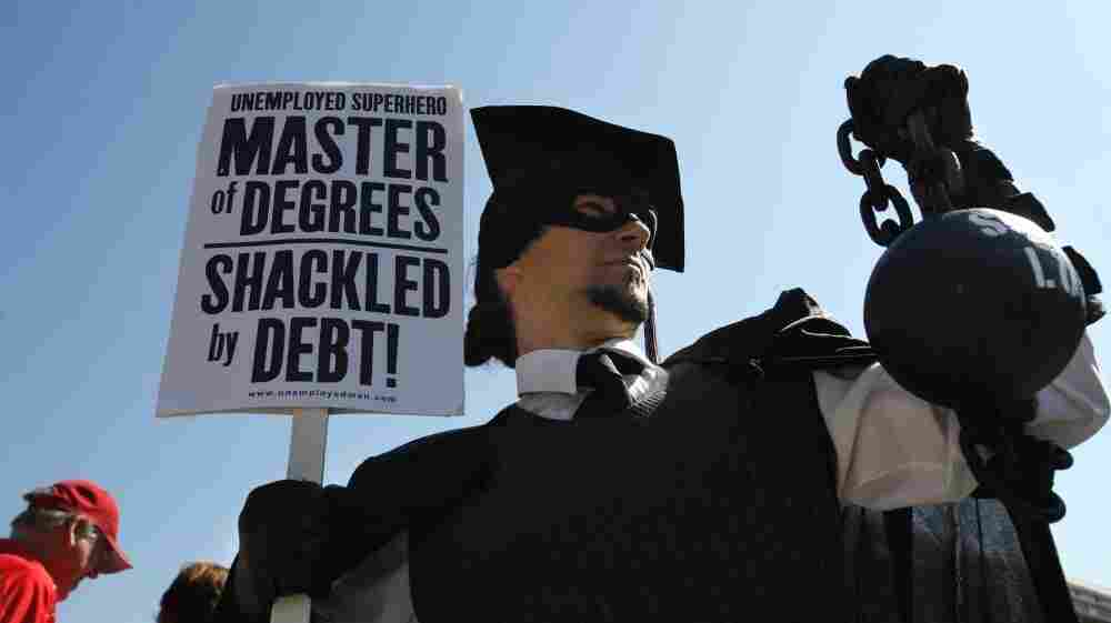"""Gan Golan of Los Angeles, dressed as the """"Master of Degrees,"""" holds a ball and chain representing his college loan debt during Occupy D.C. activities in Washington. Average in-state tuition and fees at four-year public colleges rose an additional $631 this fall, or 8.3 percent, compared with a year ago."""