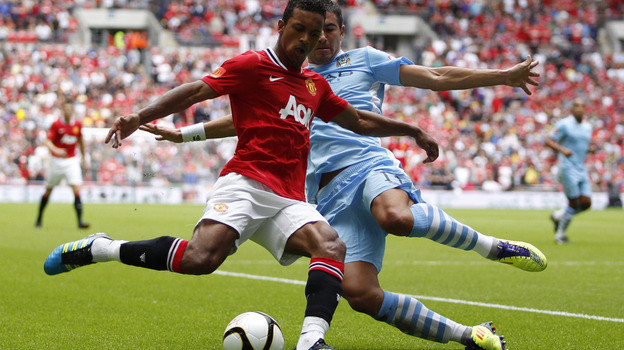 Manchester United's Nani (in red) and Manchester City's Aleksandar Kolarov during a game last August in London. (AFP/Getty Images)