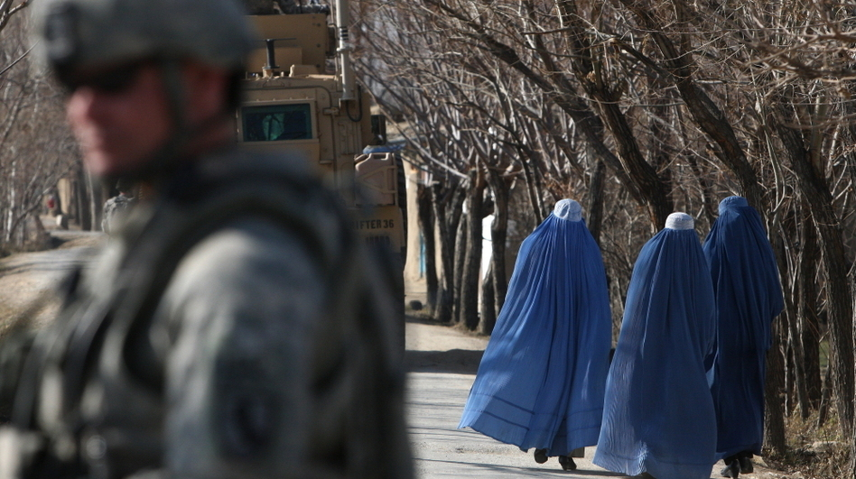 Afghan women pass U.S. soldiers near Bagram Air Base outside Kabul in 2010. While conditions for Afghan women have improved over the past decade, but they still face many restrictions, as well as abuses like honor killings. (AFP/Getty Images)