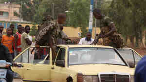 Soldiers loyal to junta leaders in Mali load their weapons, including a machine gun, onto a taxi after leaving a military camp where anti-junta forces were subdued.