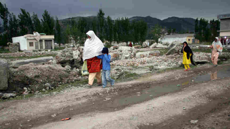 Pakistanis walk past the rubble of the demolished compound of slain al-Qaida leader Osama bin Laden in the northern town of Abbottabad this week. Bin Laden's legacy in Pakistan appears mixed. Support for al-Qaida seems to be down, but bin Laden is still revered by extremists.